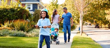 A young family walking in a suburban neighbourhood