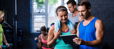 A man and woman looking at fitness software on an Ipad in a gym