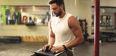 man sitting in a gym, working on his laptop