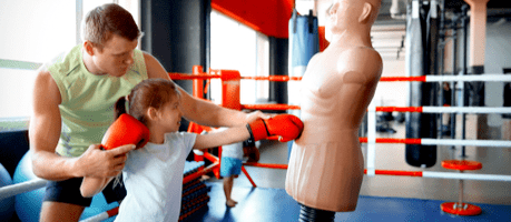 martial arts instructor teaching young girl how to punch