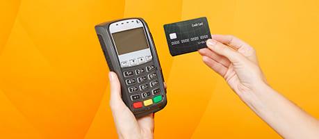 man's hand scanning a credit card at a POS terminal